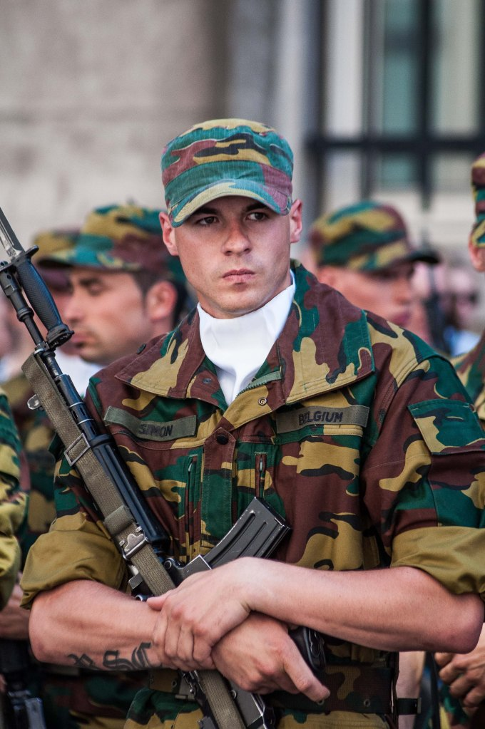 A soldier holds his rifle, as he is waiting.