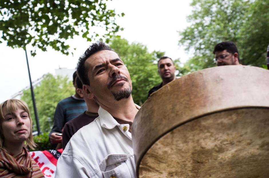 A protester makes noise with a percussion instrument.