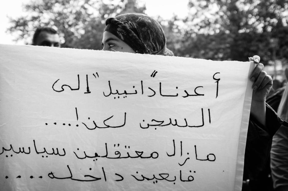 A protester holds a banner with Arabic slogans.
