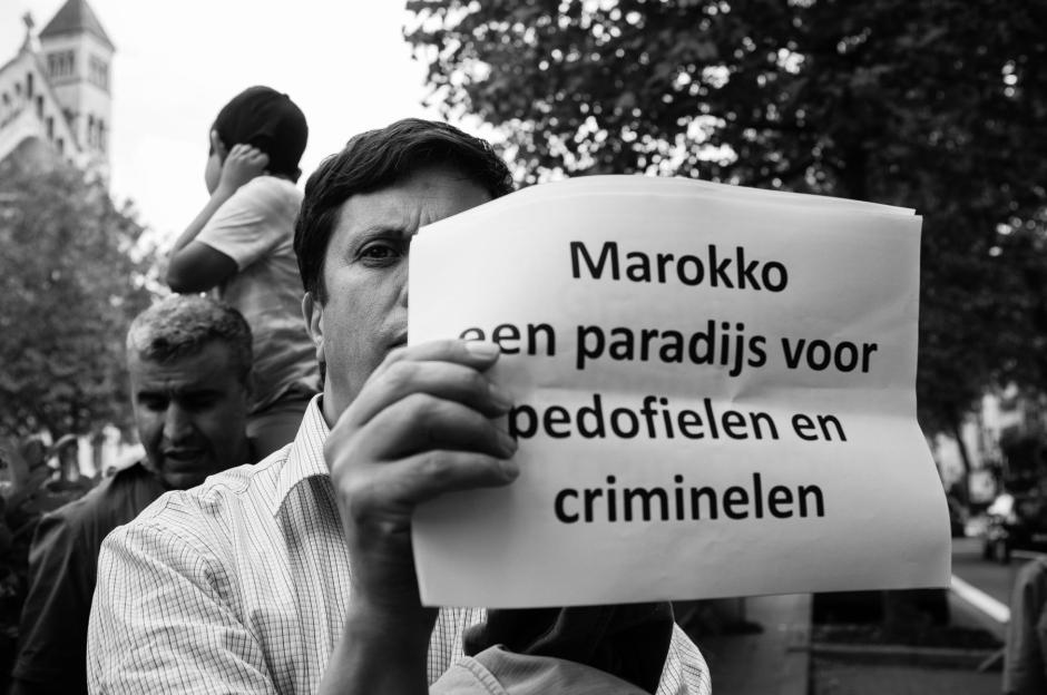 "A banner reads ""Morocco is a paradise for pedophiles and criminals."""